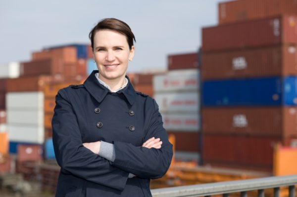 Satisfied business woman in front of cargo container terminal